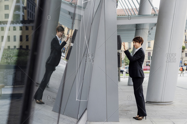 Businesswoman with short hair using ATM while reflection on modern building in city