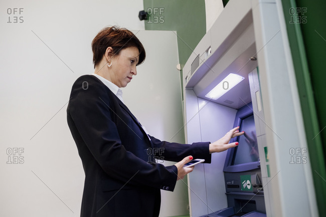 Businesswoman holding smart phone using ATM while standing by wall