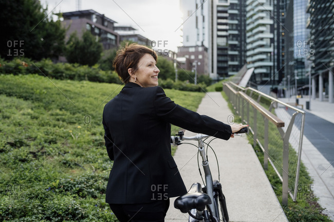 Smiling businesswoman with bicycle walking on footpath in city