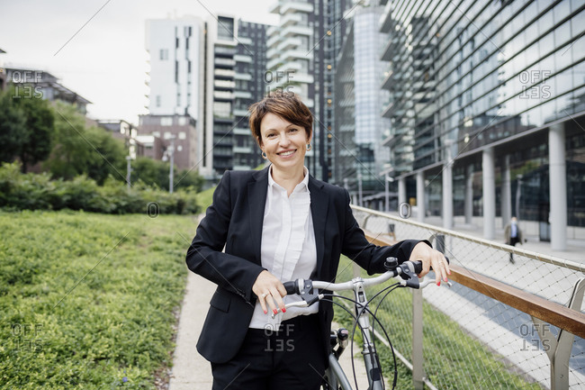Smiling female professional with bicycle standing on footpath in city