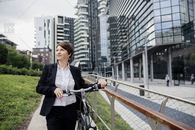 Female professional with bicycle looking away while walking against buildings in city