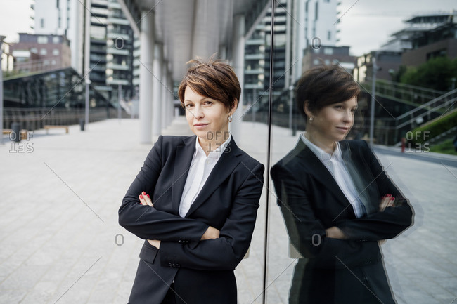 Businesswoman with arms crossed standing by modern building in city