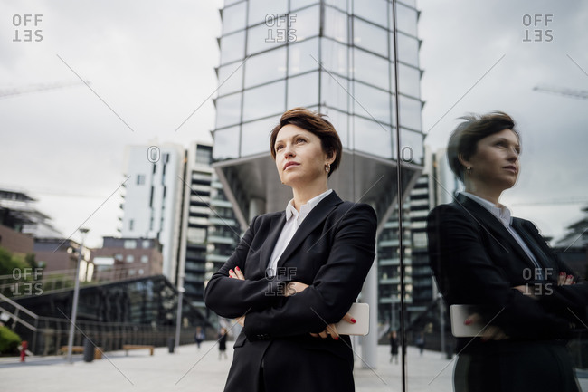 Thoughtful businesswoman with arms crossed standing by modern building in city