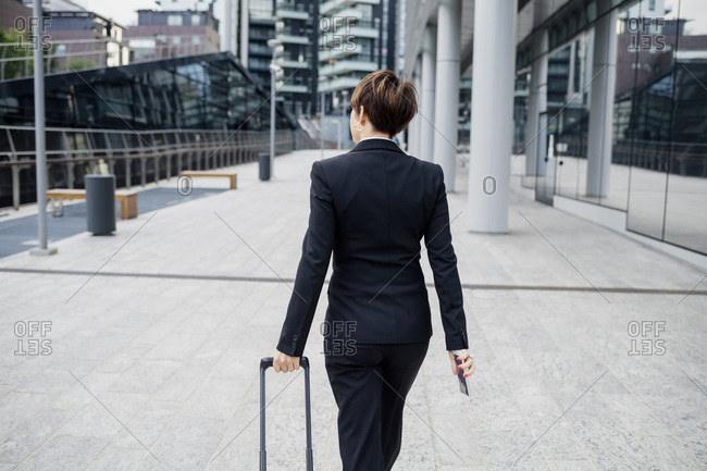Businesswoman with short hair holding suitcase while walking with footpath in city