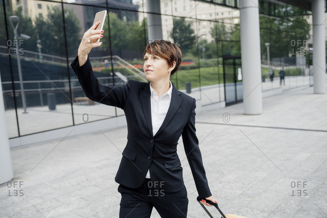 Businesswoman taking selfie with mobile phone while standing on footpath in city