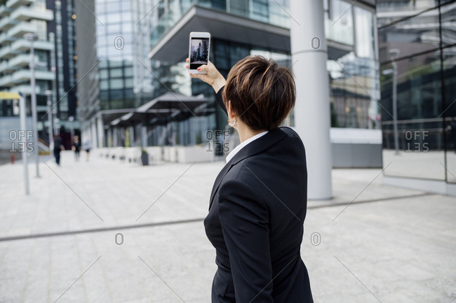 Female professional taking selfie with smart phone while standing against modern buildings in city