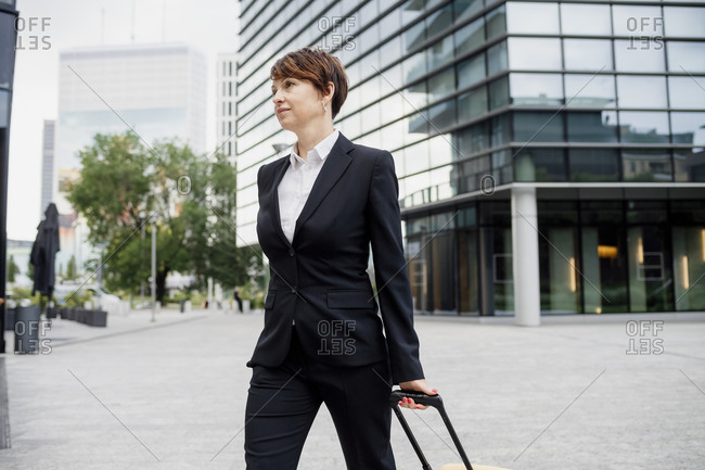 Female entrepreneur with suitcase walking on street against modern building in city