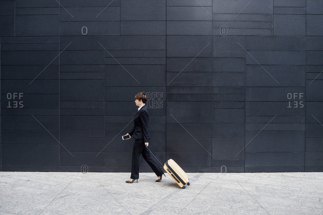 Businesswoman with suitcase walking on sidewalk by modern building in city