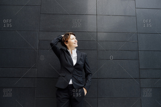 Smiling female professional with hand in hair standing against modern building