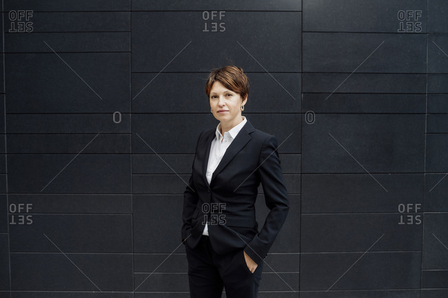 Confident female professional with hands in pockets standing against modern building