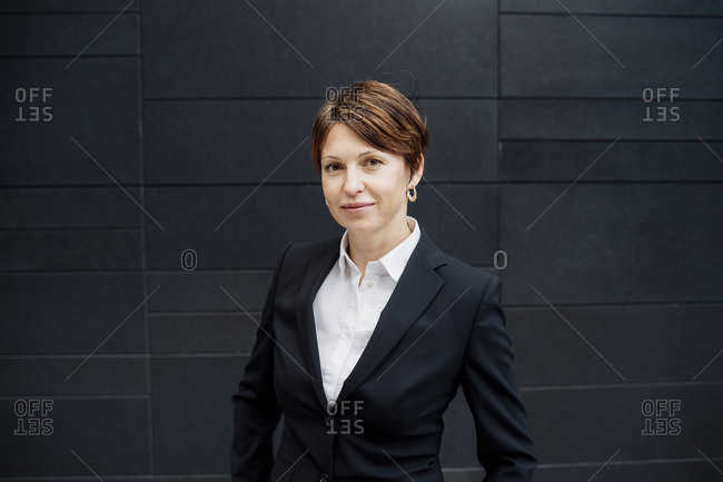 Confident businesswoman with short hair standing against modern building in city