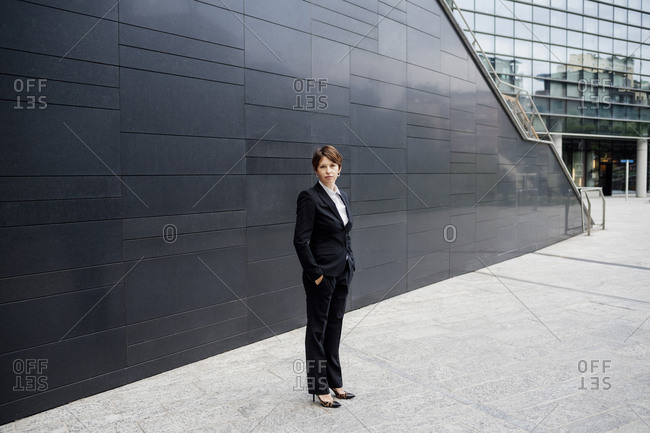 Confident businesswoman standing on sidewalk against modern buildings in city