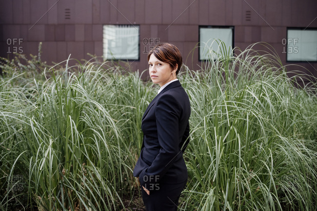 Businesswoman with short hair standing by plants in city