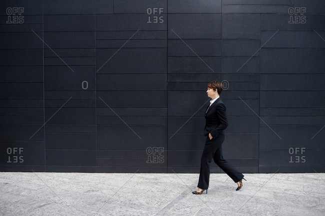 Businesswoman with short hair walking on sidewalk by modern building in city