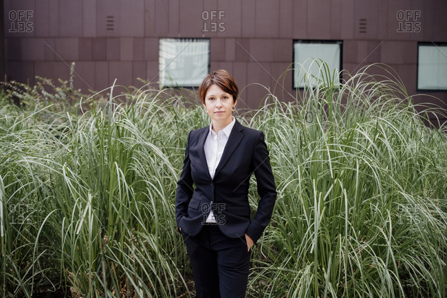 Confident businesswoman with hands in pockets standing by plants against building