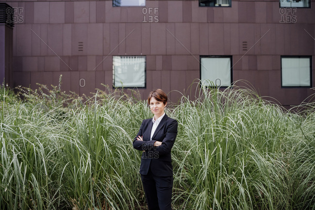 Confident businesswoman with arms crossed standing by plants in city
