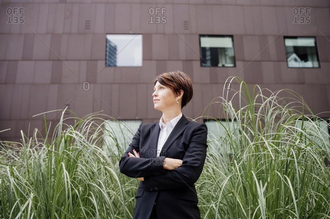 Thoughtful businesswoman with arms crossed standing by plants against building in city