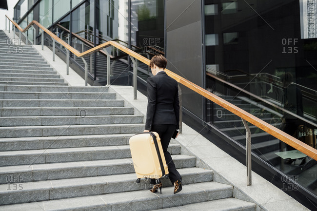 Businesswoman with suitcase walking on steps in city
