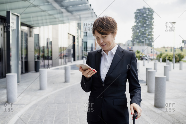 Female entrepreneur with short hair using mobile phone while standing on sidewalk in city
