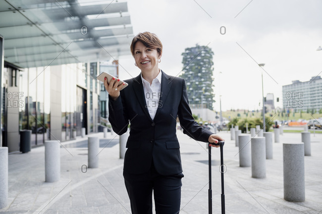 Smiling businesswoman talking over mobile phone while standing on sidewalk in city