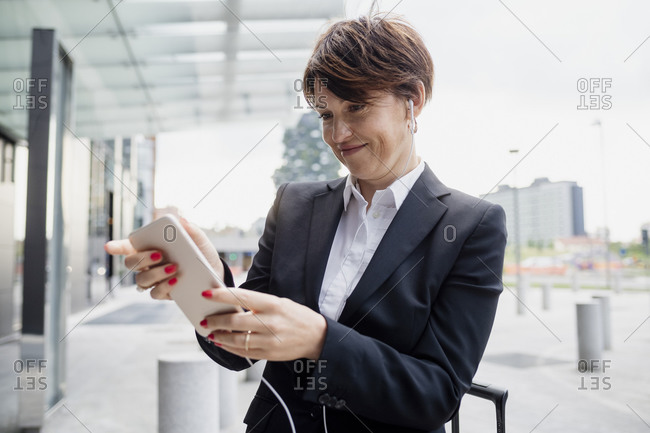 Close-up of female professional wearing headphones using mobile phone while standing in city