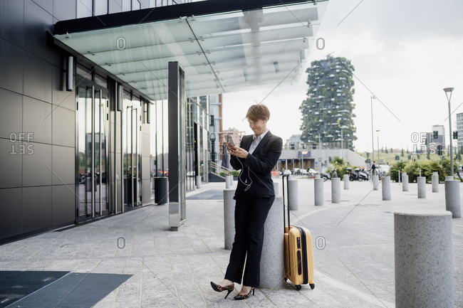 Female entrepreneur using smart phone while standing by column in city