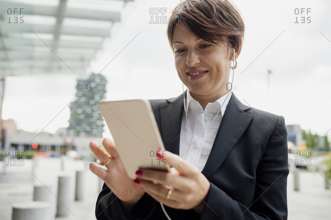 Close-up of businesswoman using mobile phone while listening music through headphones against sky