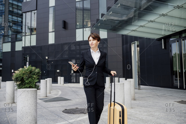 Female professional listening music while walking with suitcase against modern building