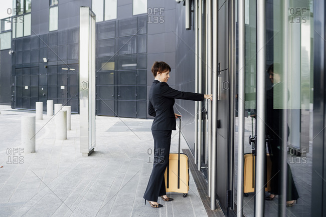 Businesswoman with suitcase entering in modern building