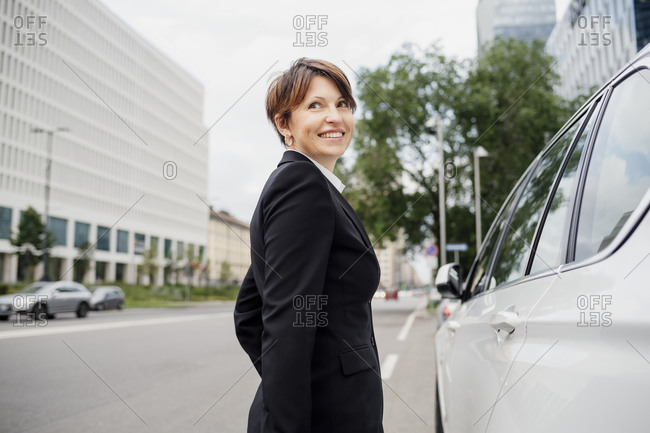 Smiling businesswoman with short hair standing by car on street in city