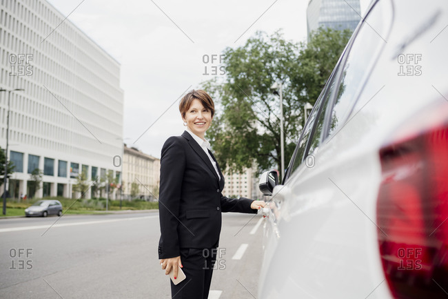 Smiling female professional standing by car on street in city