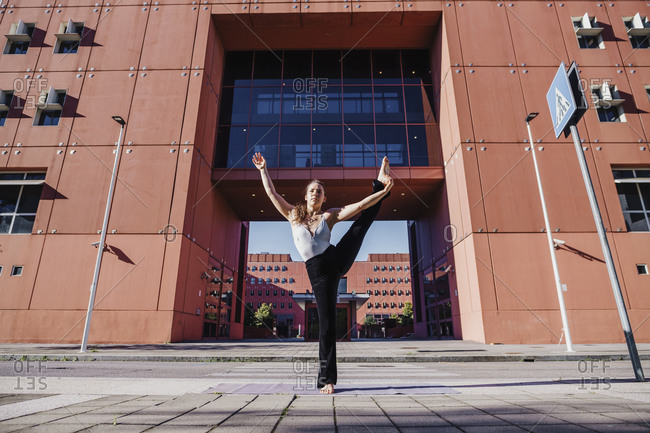 Young woman performing yoga in hand to big toe pose on city street