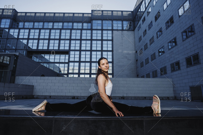 Young woman practicing splits in modern city
