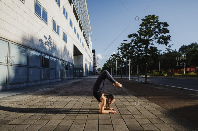 Young woman performing yoga on sidewalk in city during sunny day