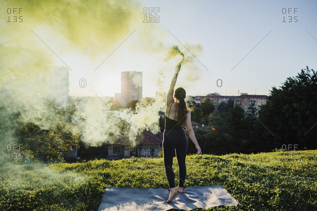 Sporty young woman holding distress flare at city park during sunny day