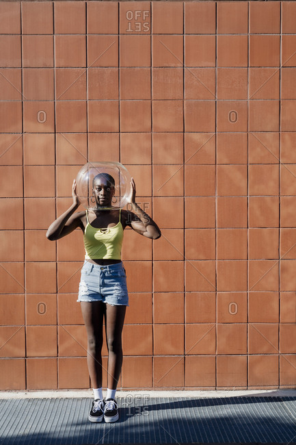 Young woman holding glass container over head while standing against building in city