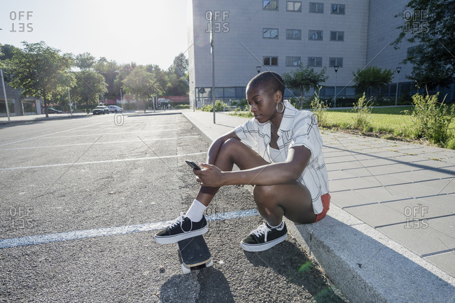 Young woman using smart phone while sitting with skateboard on footpath in city