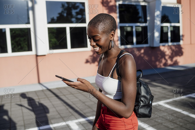 Cheerful young woman with shaved head using smart phone while walking on sidewalk in city