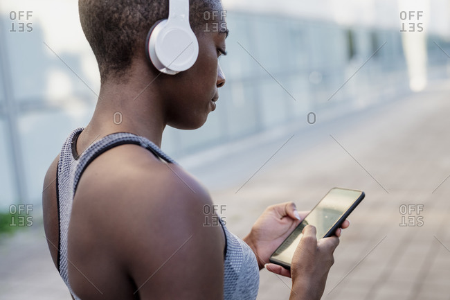 Close-up of young woman wearing headphones using smart phone while standing in city