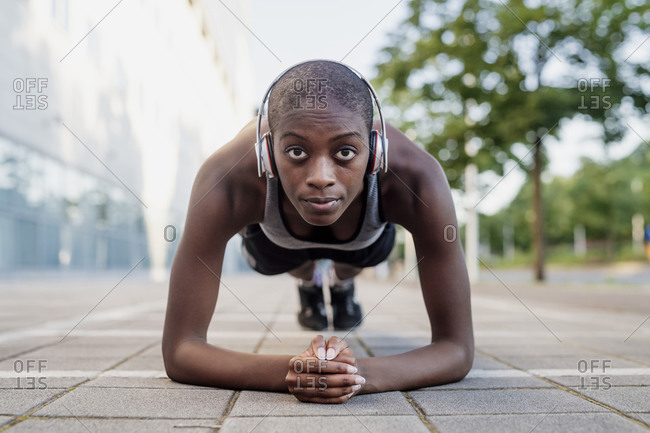 Confident woman with shaved head listening music while doing squads on footpath