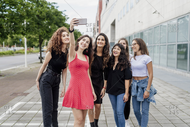 Smiling young woman taking selfie with female friends while standing on footpath in city