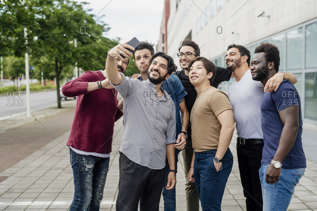 Man taking selfie with male friends while standing on footpath in city