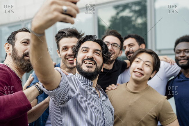 Cheerful man taking selfie with male friends while standing in city