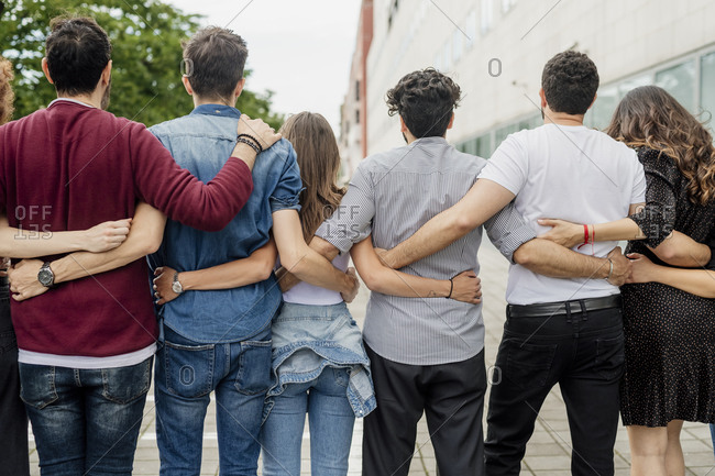 Male and female friends with arms around standing on footpath in city