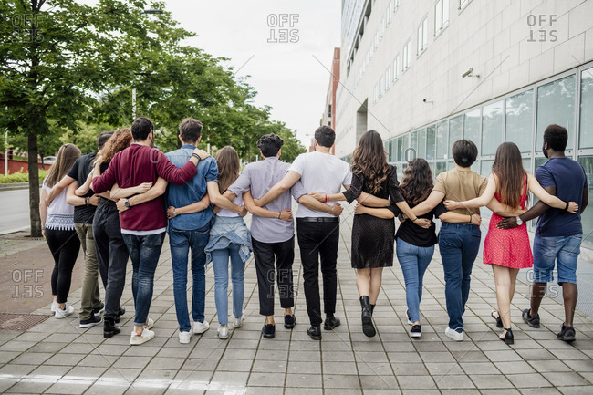 Female and male friends with arms around walking on footpath in city