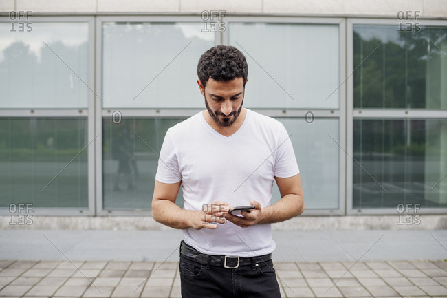 Handsome mid adult man using smart phone while standing on footpath against building