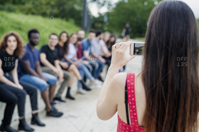 Woman photographing friends sitting in row with smart phone at park