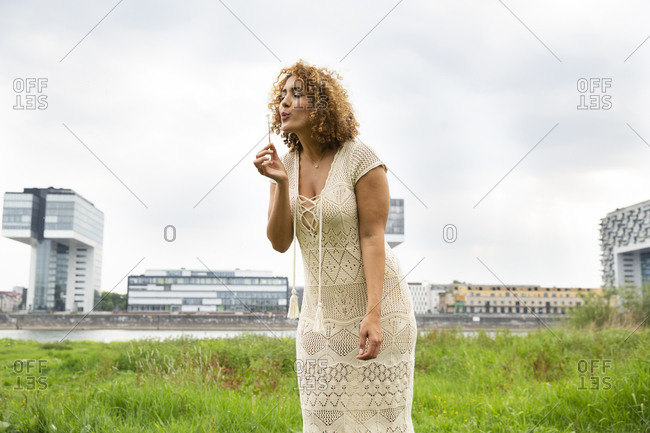 Mid adult woman with curly hair blowing flower while standing on grassy land against sky
