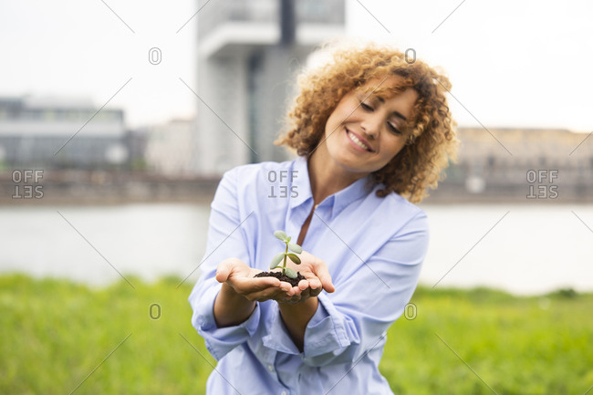 Smiling businesswoman with curly hair holding small plant while standing against sky in city