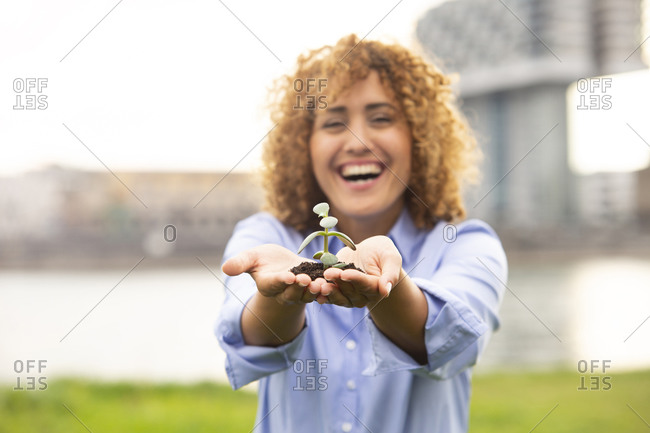 Cheerful businesswoman with curly hair holding small plant while standing in city